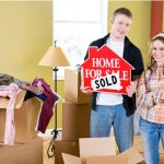 Young couple holding home sold sign.