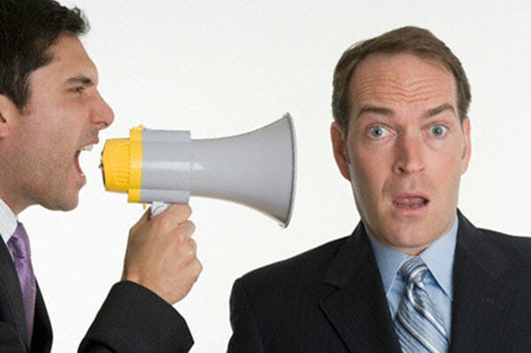 man with bullhorn yelling at businessman
