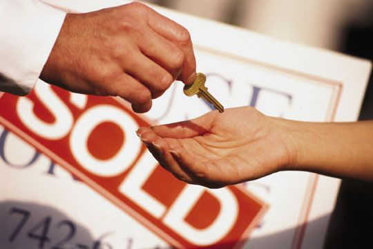 Real Estate Agent Giving Key to Home Buyer